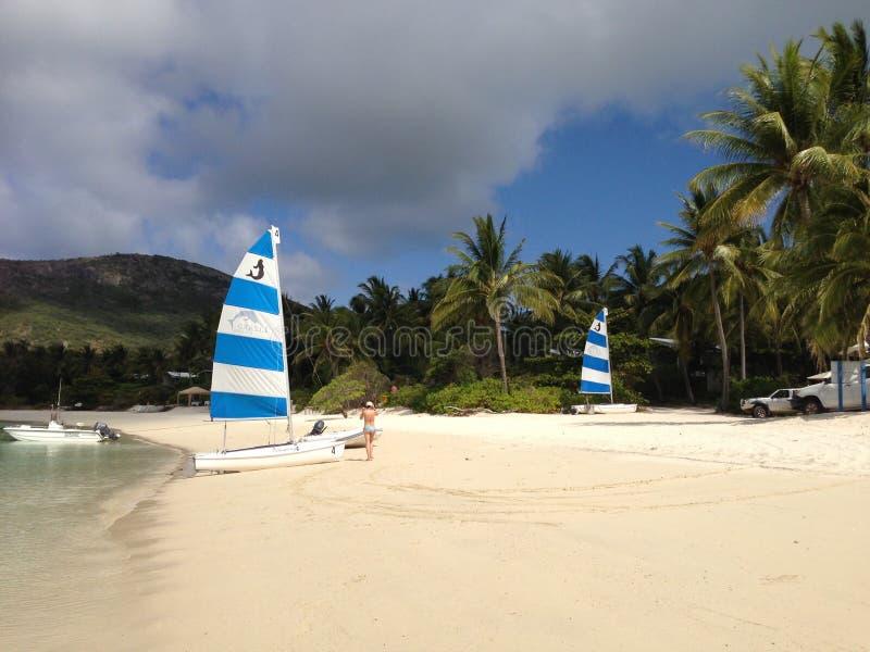 在一个热带海岛上的小船、妇女和棕榈树靠岸 免版税库存图片