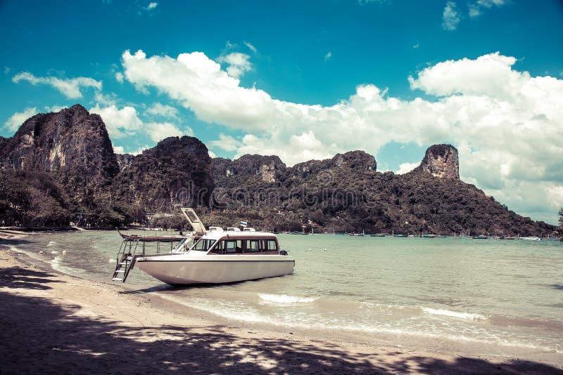 在一个热带海岛的岸的雪白豪华快艇 停泊在一个沙滩、热带和岩石在背景中 Krabi 图库摄影