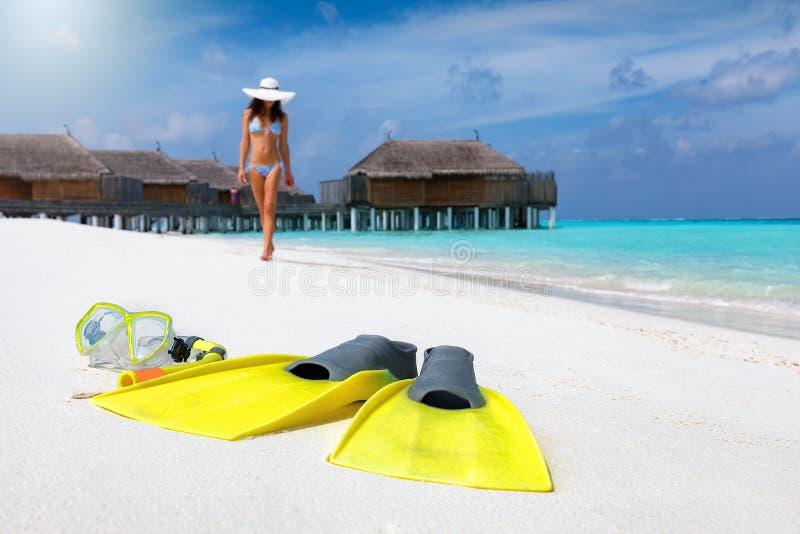 在一个热带海滩的潜航的齿轮与比基尼泳装的妇女走在背景中的 免版税图库摄影