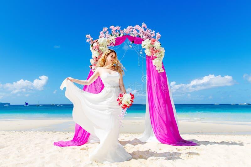 在一个热带海滩的婚礼在紫色 愉快的白肤金发的brid 免版税库存图片