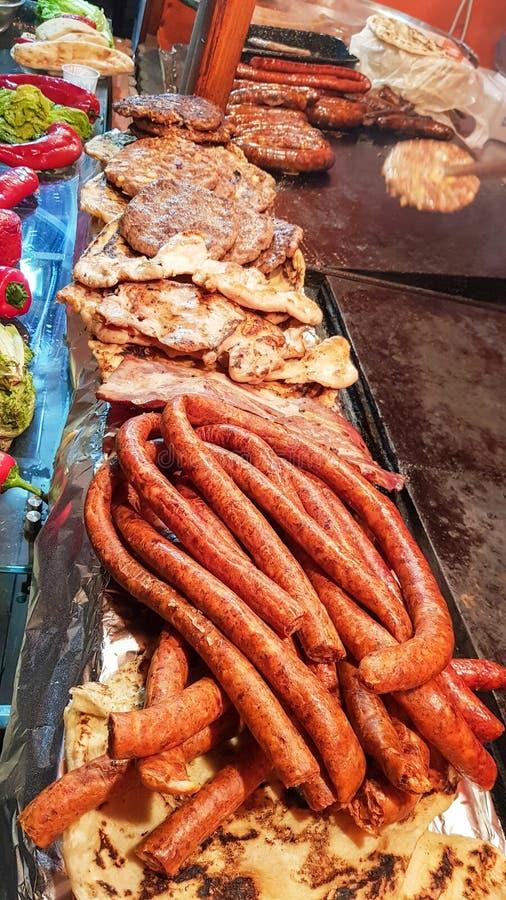 在一个热的格栅板的未加工和烤混杂的肉食物在一个室外市场上 免版税库存照片