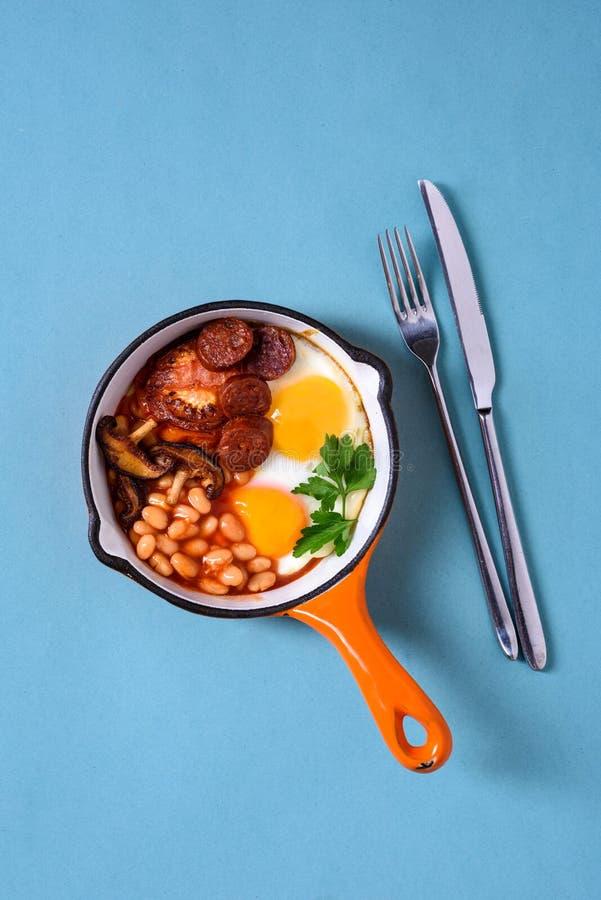 在一个烹调平底锅的英式早餐,煎蛋,香肠,豆 库存图片