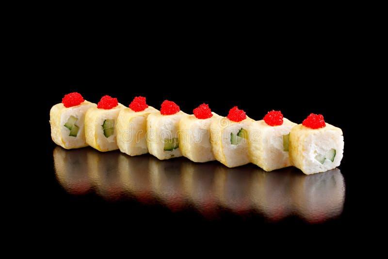 在一个煎蛋卷的原始的寿司卷用乳脂干酪和黄瓜在黑背景 图库摄影