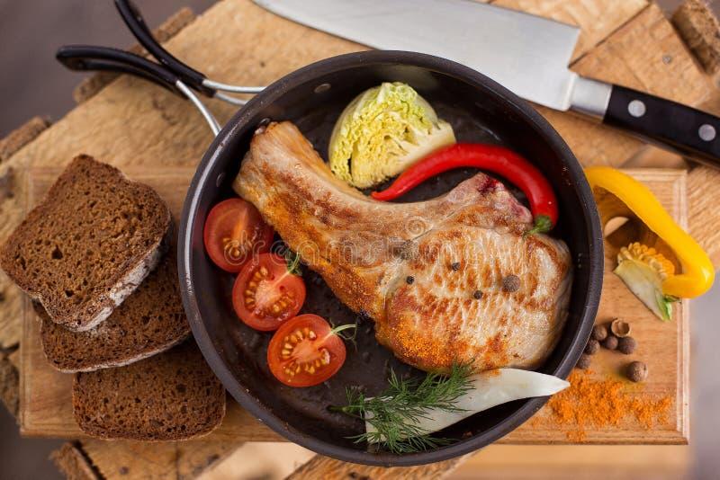 在一个煎锅的油煎的肉,有菜和香料的 乡村模式 免版税库存照片