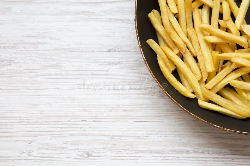 在一个煎锅的炸薯条在白色木背景,顶视图 库存图片