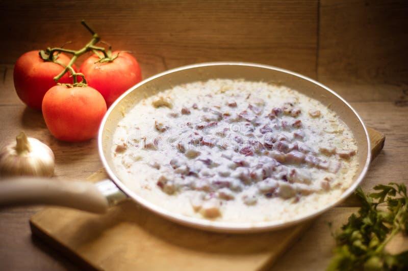 在一个煎锅的白汁在温暖的光 库存照片