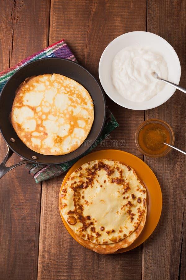 在一个煎锅的薄煎饼有酸性稀奶油和蜂蜜的 图库摄影