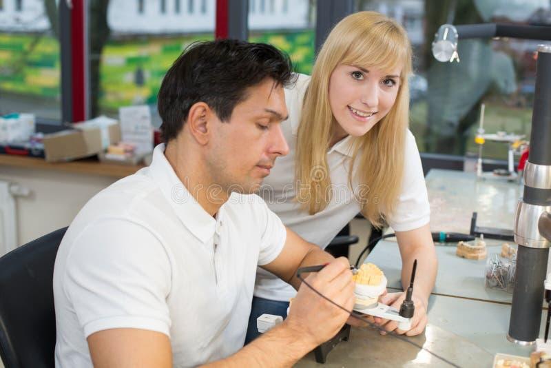 在一个牙齿实验室注意技术人员的学徒工作 免版税库存图片