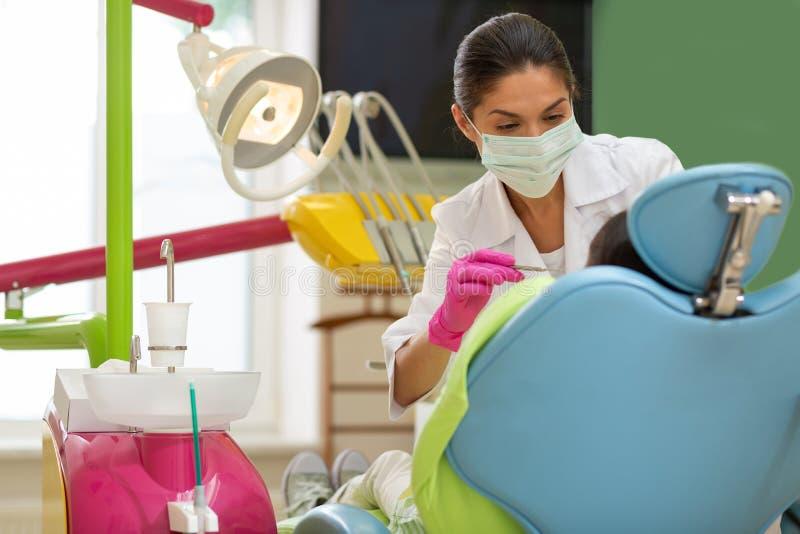 在一个牙齿钻子附近的严肃的女性牙医身分 免版税库存照片