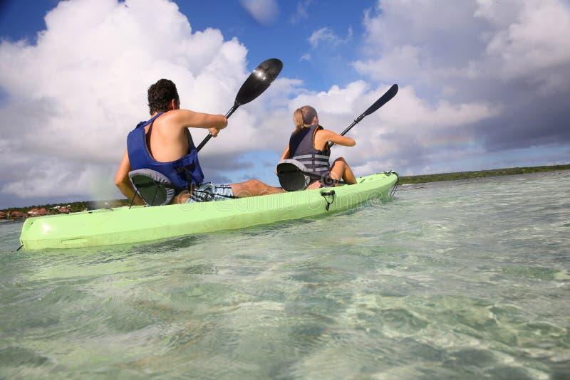 在一个独木舟的夫妇划船在热带 免版税库存图片
