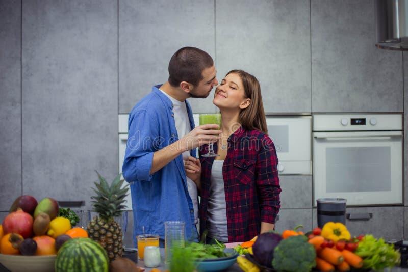 在一个现代厨房里,有两三的在早晨i饮料圆滑的人和微笑的美好的设计在彼此 库存照片