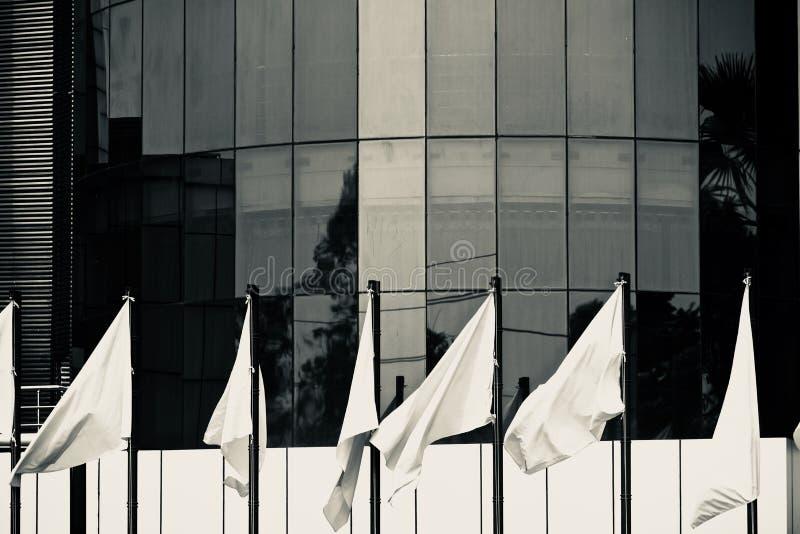 在一个现代建筑大厦前面的白旗拍摄 库存照片