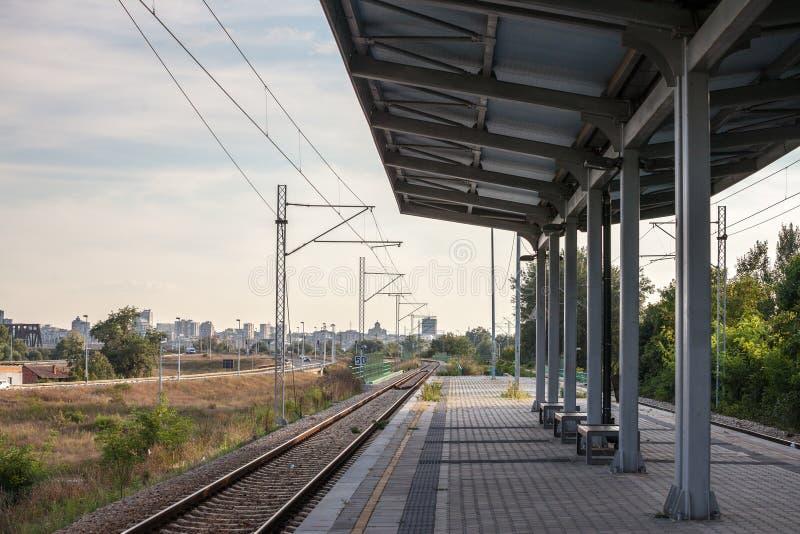 在一个现代火车站的平台风雨棚在贝尔格莱德,塞尔维亚通勤者铁路系统的一条郊区被使充电的线  免版税图库摄影