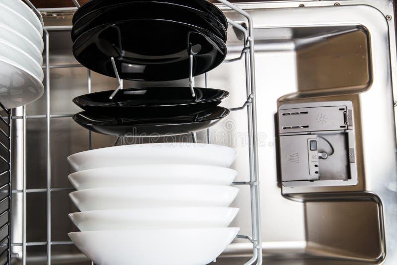 在一个现代洗碗机机器的盘 免版税库存图片
