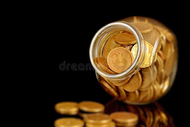 在一个玻璃大瓶的硬币在黑背景小景深 免版税库存图片
