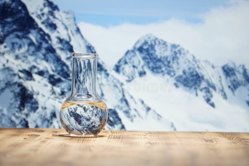 在一个玻璃实验室烧瓶的净水在冬天山背景的木桌上 生态概念,测试  免版税库存图片