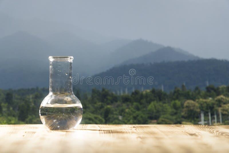 在一个玻璃实验室烧瓶的净水在山背景的木桌上 生态概念,纯净测试  免版税库存图片