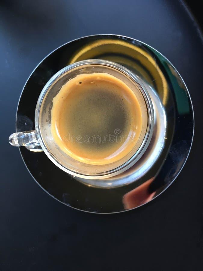 在一个玻璃杯子的咖啡在灰色桌上的一个金属茶碟 库存照片