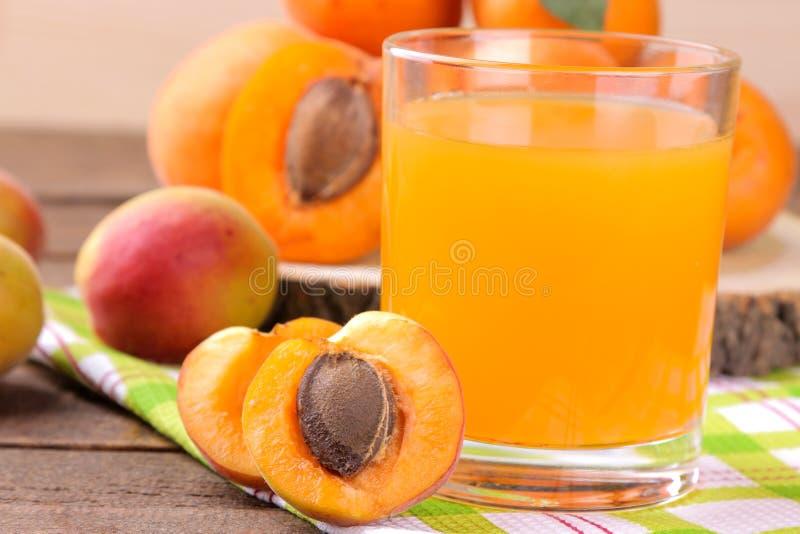 在一个玻璃杯子的杏子汁在棕色木背景的新鲜的杏子旁边 免版税库存图片