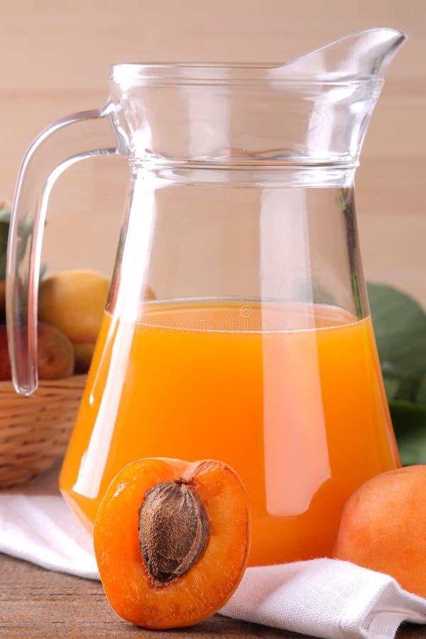 在一个玻璃杯子的杏子汁在棕色木背景的新鲜的杏子旁边 库存图片