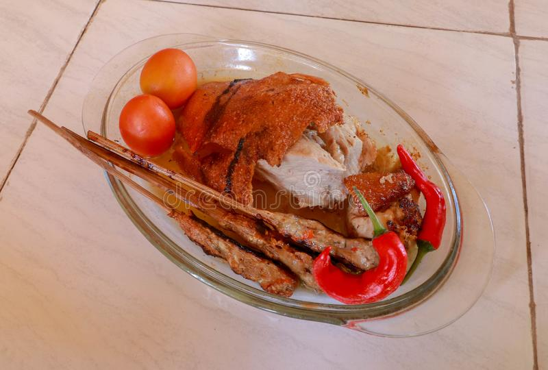 在一个玻璃烤平底锅的烤肉 在一根木棍子的肉末 嘎吱咬嚼和金黄被烘烤的皮肤 辣椒和新鲜的toma 免版税图库摄影