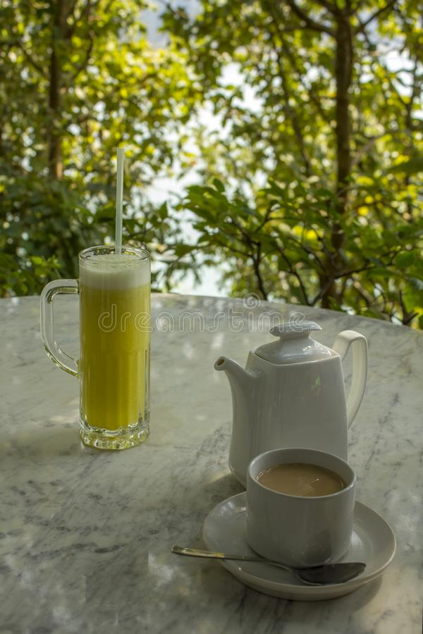 在一个玻璃烧杯的明亮的黄色饮料有秸杆和一个杯子的有牛奶饮料的在一个白色陶瓷茶壶附近在一张大理石桌上在a 图库摄影