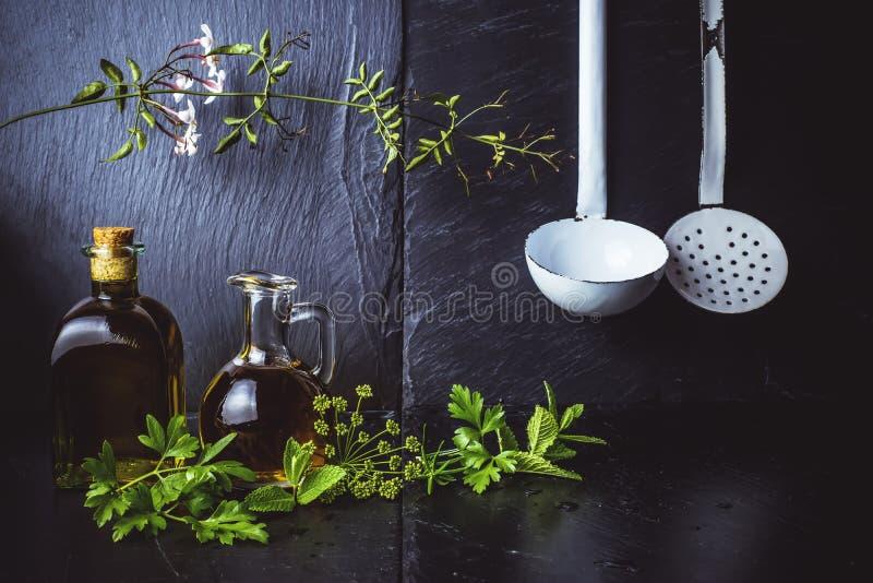 在一个玻璃瓶子和瓶的维尔京橄榄油用草本和花 免版税库存图片