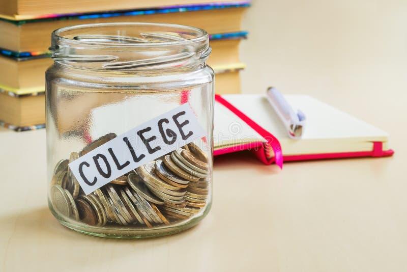 在一个玻璃瓶子在一支白色圆珠笔附近和少量书的很多硬币和学院词在桌上 学院的攒钱和 免版税库存照片