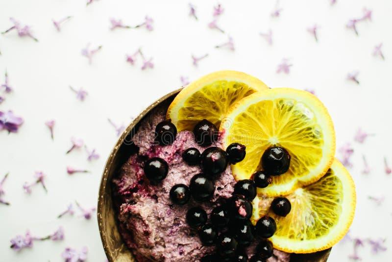 在一个玻璃瓶子的健康圆滑的人碗早餐有淡紫色花的 库存照片