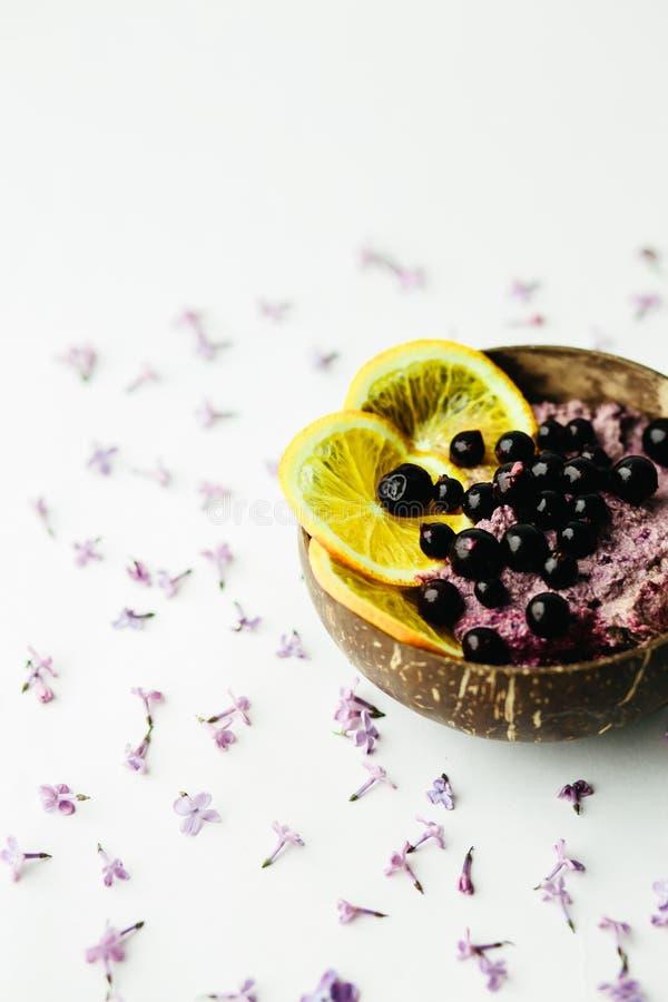 在一个玻璃瓶子的健康圆滑的人碗早餐有淡紫色花的 免版税图库摄影