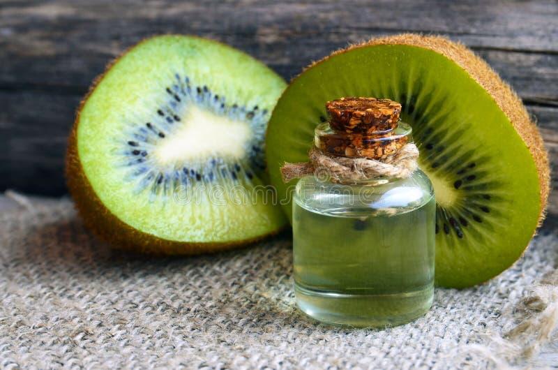 在一个玻璃瓶子的根本猕猴桃菜籽油用在老木背景的新鲜的被对分的猕猴桃 芳香疗法,温泉,秀丽治疗和 免版税图库摄影