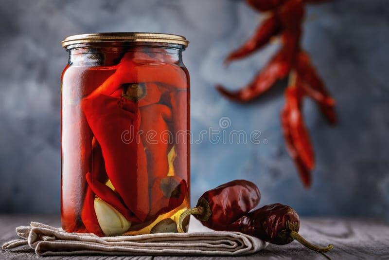 在一个玻璃瓶子的用卤汁泡的红辣椒在一个木板 免版税库存图片