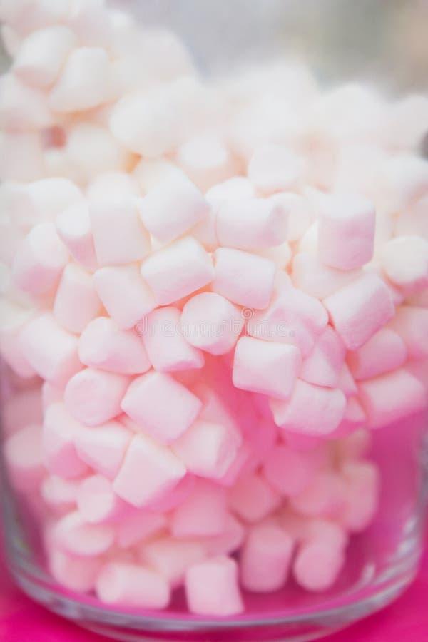 在一个玻璃瓶子的白色蛋白软糖在桃红色背景 免版税库存照片