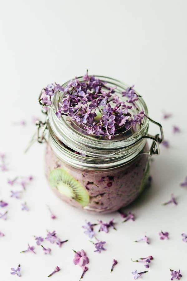 在一个玻璃瓶子的紫色健康圆滑的人早餐有淡紫色花的 库存图片