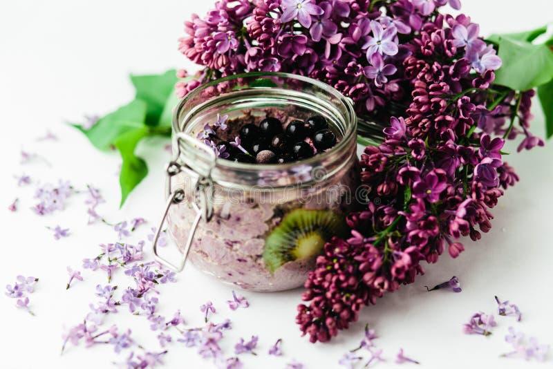 在一个玻璃瓶子的紫色健康圆滑的人早餐有淡紫色花的 库存照片