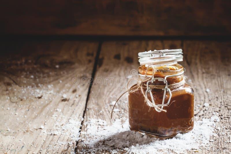 在一个玻璃瓶子的自创盐味的焦糖有盒盖的,被洒的婆罗双树 免版税库存照片
