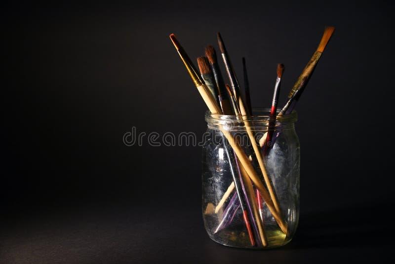在一个玻璃瓶子的艺术家的刷子在黑暗的背景 免版税图库摄影