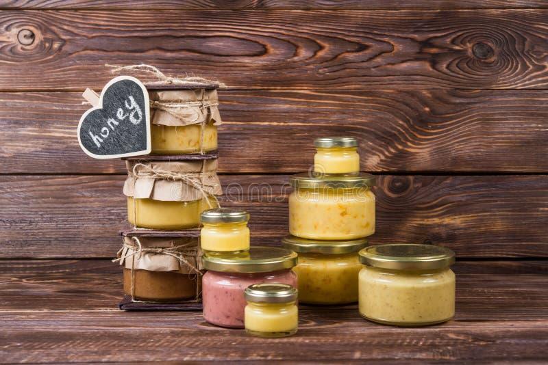 在一个玻璃瓶子的蜂蜜在一个黑暗的木背景ï ¿ ½ halk板 免版税库存图片