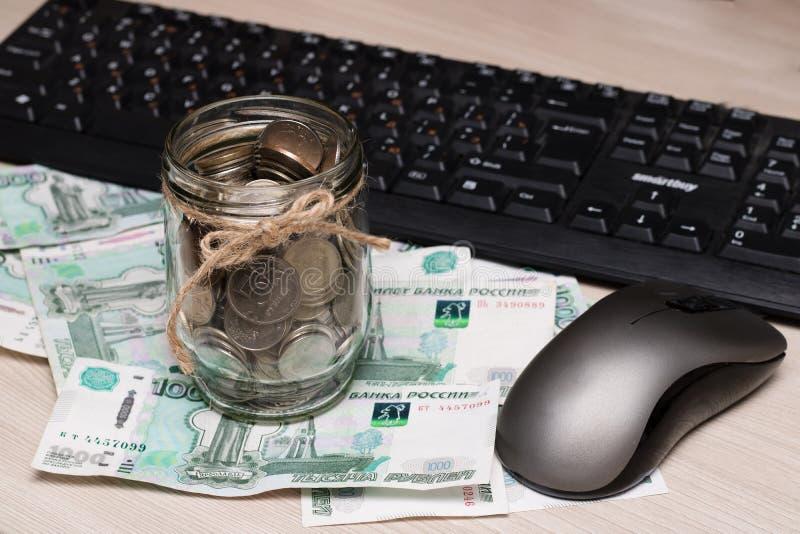 在一个玻璃瓶子的金属硬币反对一在桌上的一千卢布的纸衡量单位背景在键盘附近 库存照片