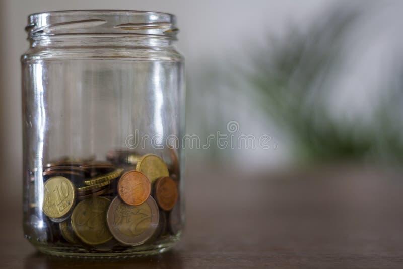 在一个玻璃瓶子的金钱在一张木桌上 库存图片