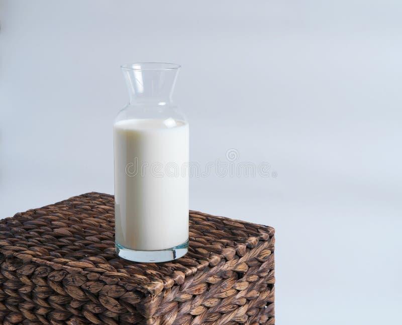在一个玻璃瓶的牛奶在一个柳条箱子站立 库存照片