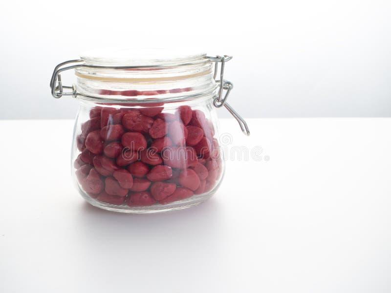 在一个玻璃瓶的红色石头 库存照片