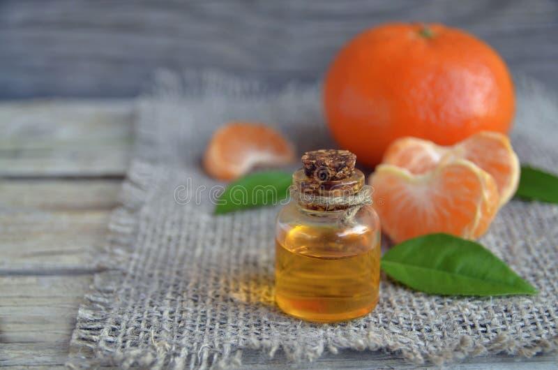 在一个玻璃瓶的蜜桔精油用在老木桌上的新鲜水果 图库摄影