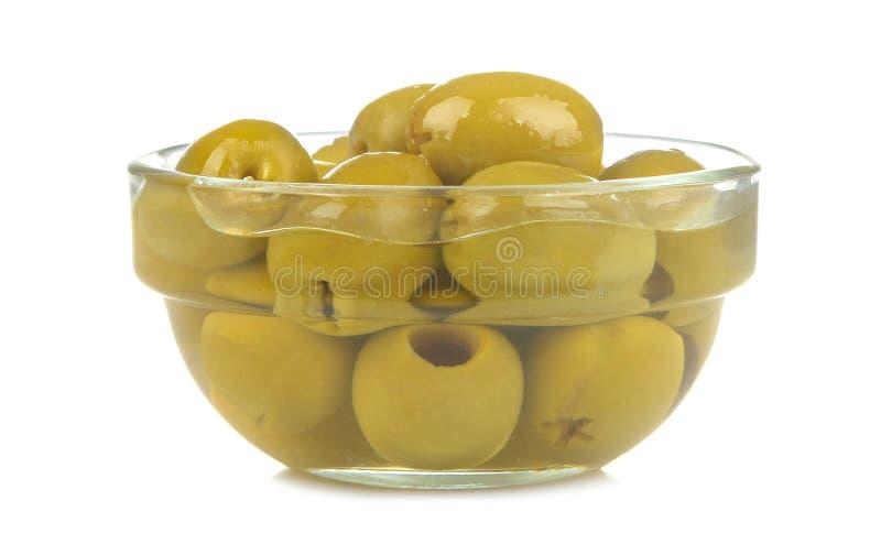在一个玻璃碗特写镜头的绿橄榄在白色被隔绝的背景 免版税库存照片