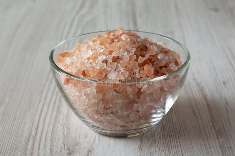 在一个玻璃碗的喜马拉雅海盐在白色木背景,侧视图 免版税库存图片