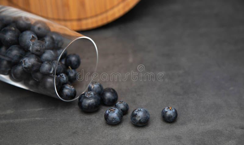 在一个玻璃碗的新鲜的蓝莓 从一个玻璃杯子驱散的可口蓝莓 灰色背景在背景中是木的 免版税库存照片