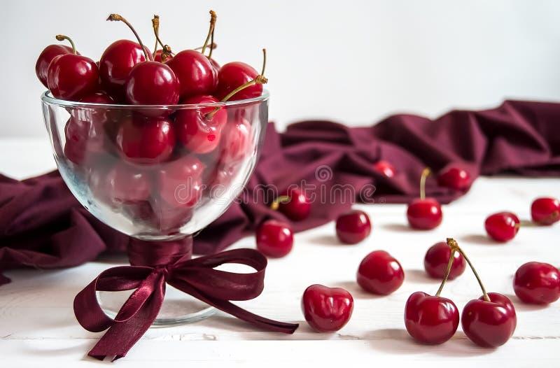 在一个玻璃碗的甜樱桃在与餐巾的轻的背景 库存照片