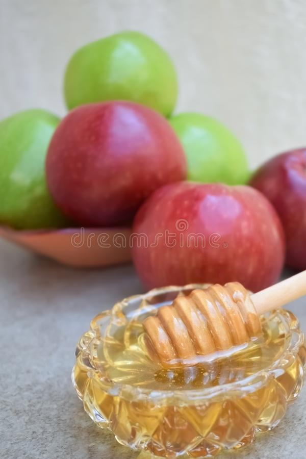在一个玻璃碗的蜂蜜和五颜六色的苹果在背景中 免版税图库摄影