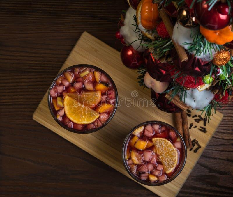 在一个玻璃觚,加香料的热葡萄酒的芬芳辣传统饮料,与圣诞树、香料和新鲜水果 库存照片