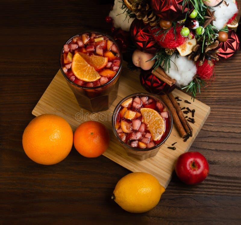 在一个玻璃觚,加香料的热葡萄酒的芬芳辣传统饮料,与圣诞树、香料和新鲜水果 免版税图库摄影